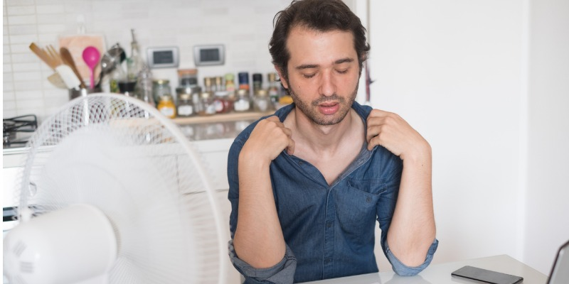 Man cooling off in front of fan