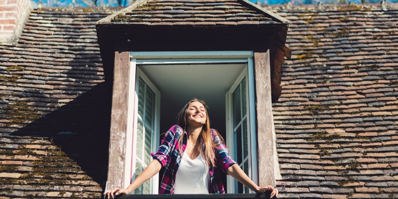 Young woman standing with windows open